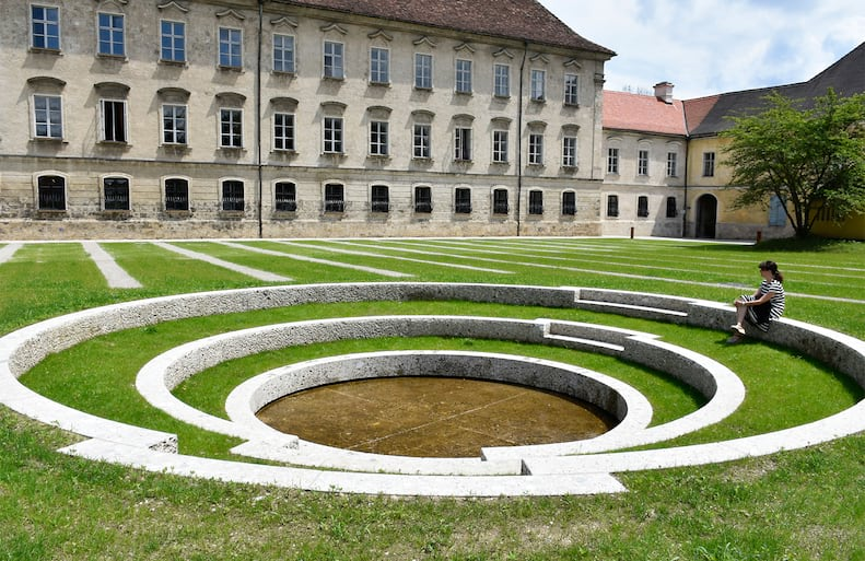 Moderne Brunnenanlage aus Naturstein Nagelfluh in historischer Bauumgebung